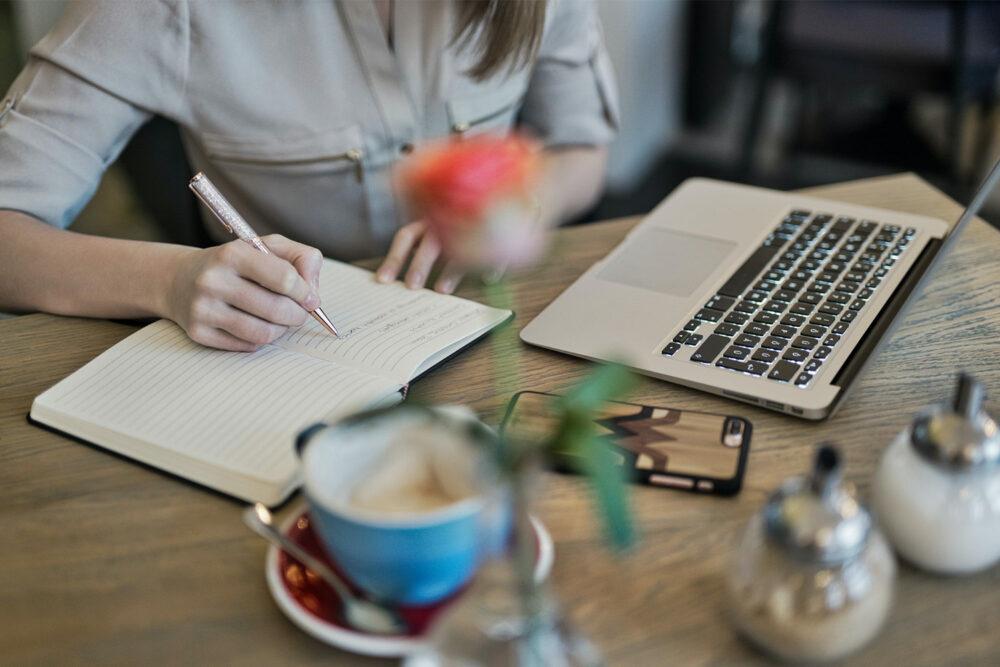 Kvinna som skriver copy i anteckningsblock för sin content marketing